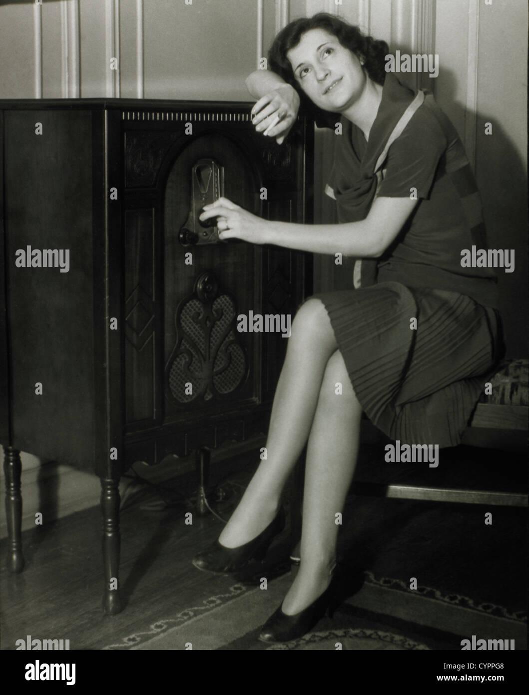 La donna si ascolta la radio 1930 Immagini Stock