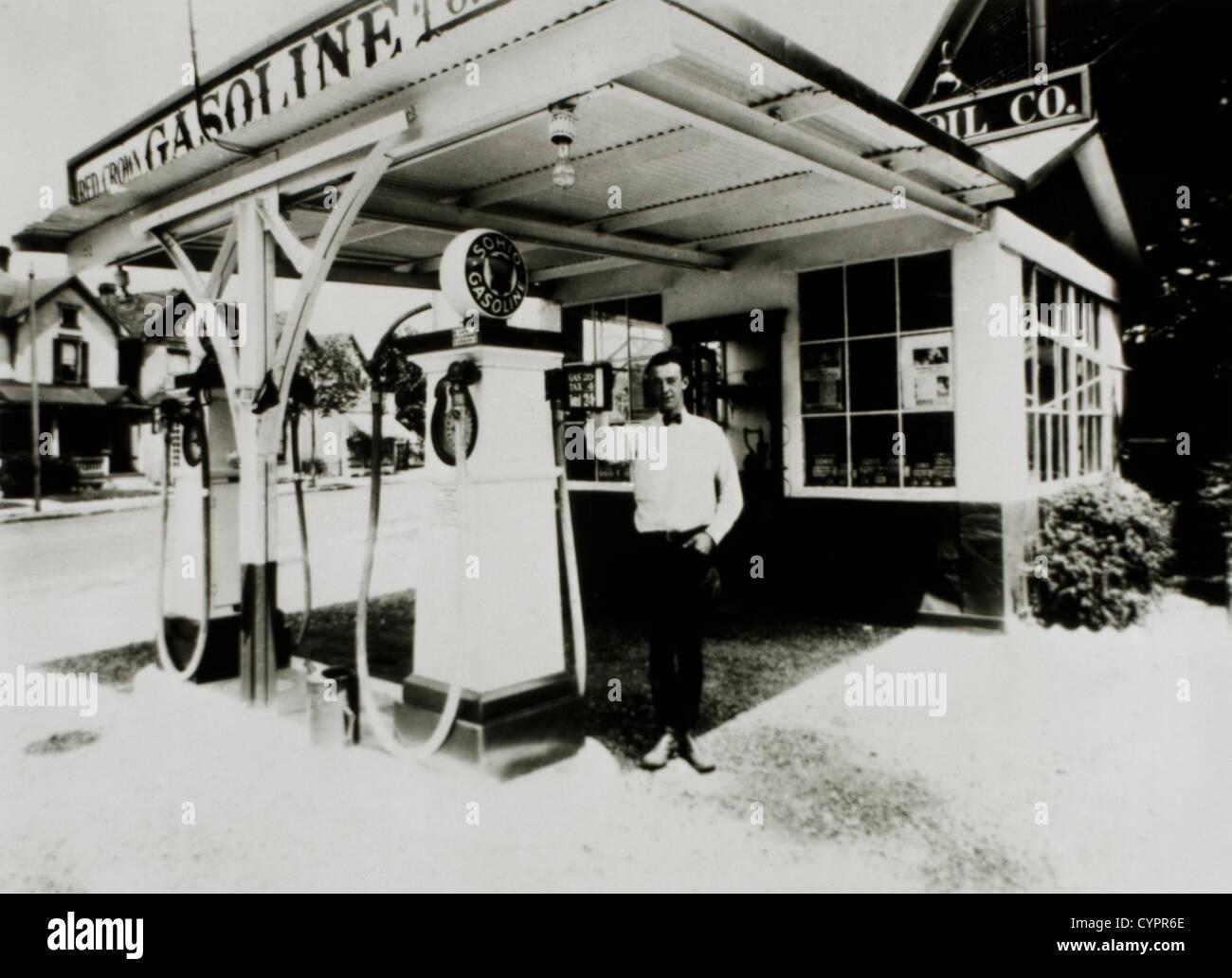 Uomo in piedi accanto alla pompa di benzina alla stazione di benzina, Dayton, Ohio, USA, 1931 Immagini Stock