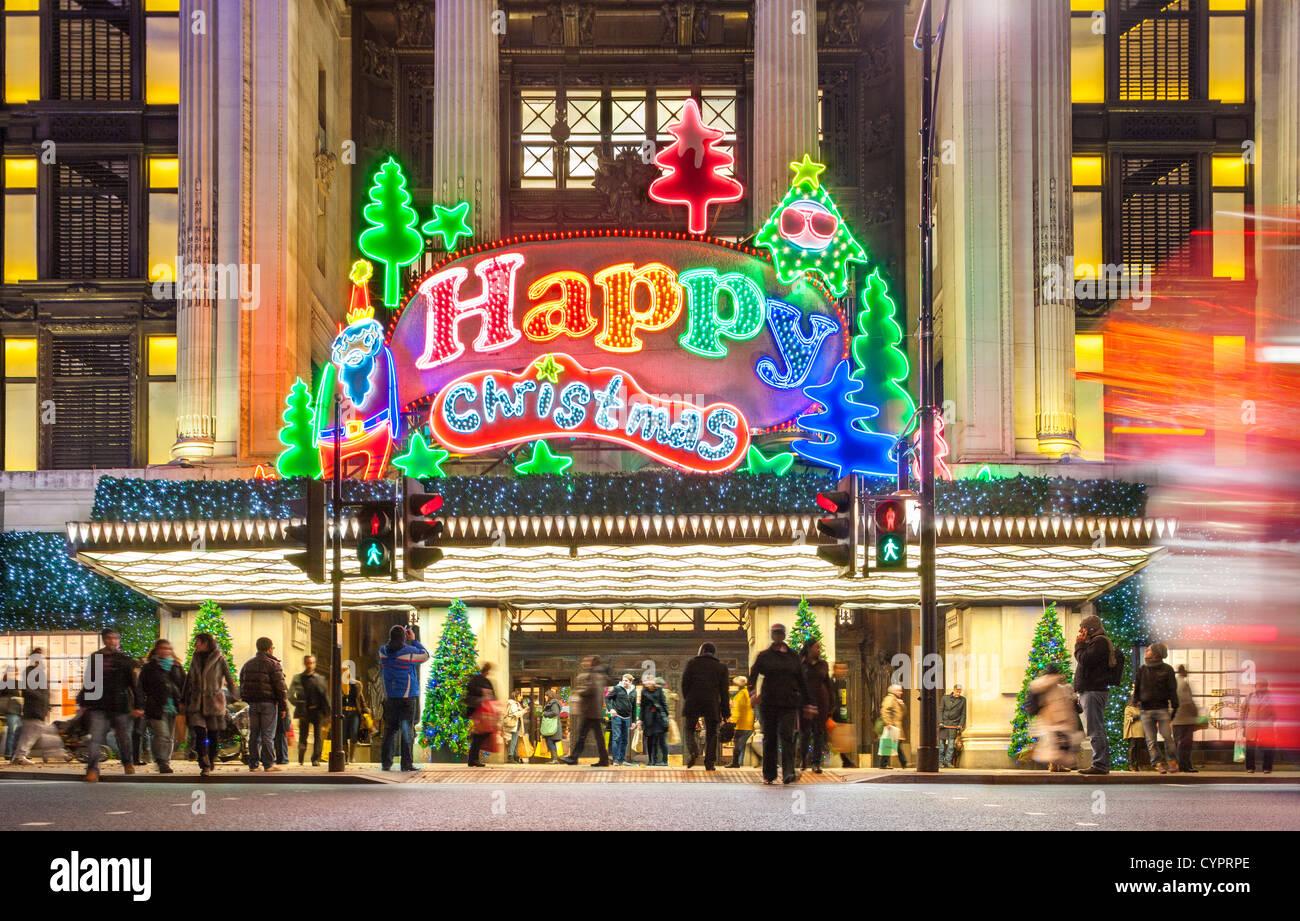 Londra REGNO UNITO. Christmas Shopper xmas shopping a Selfridge store Oxford Street con grande insegna al neon lights Immagini Stock