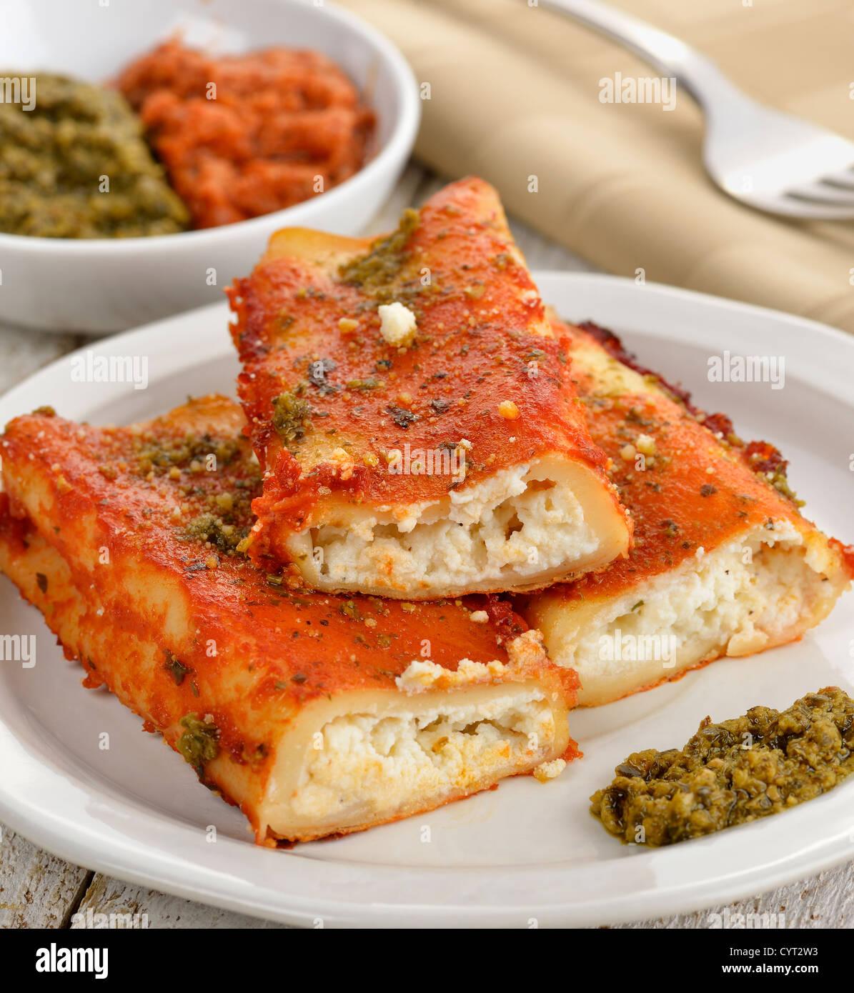 Cannelloni con formaggio , la salsa di pomodoro e pesto di basilico Immagini Stock