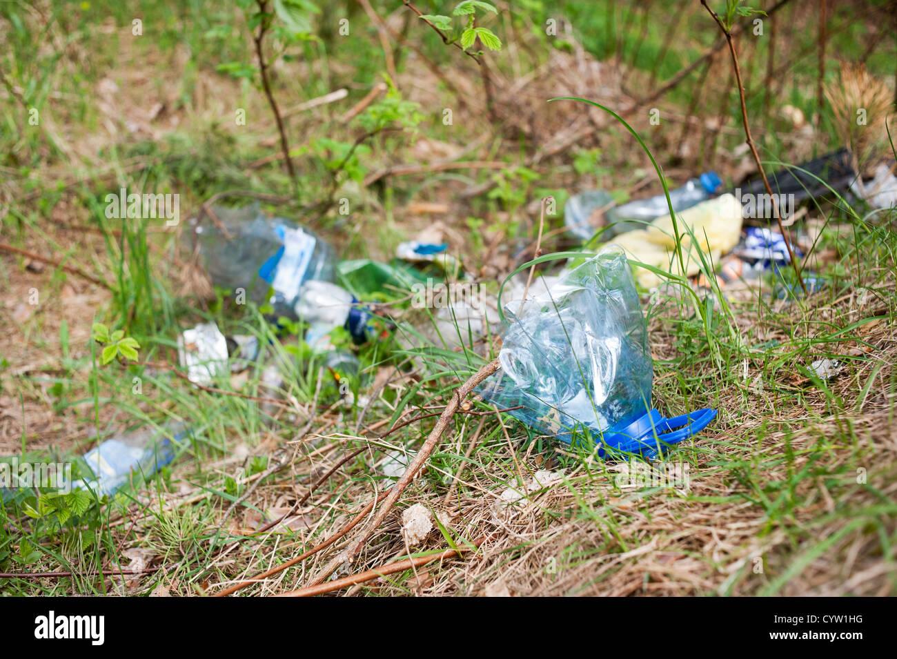 Diffusione illegale di rifiuti in erba, blu bottiglia di plastica dump Immagini Stock