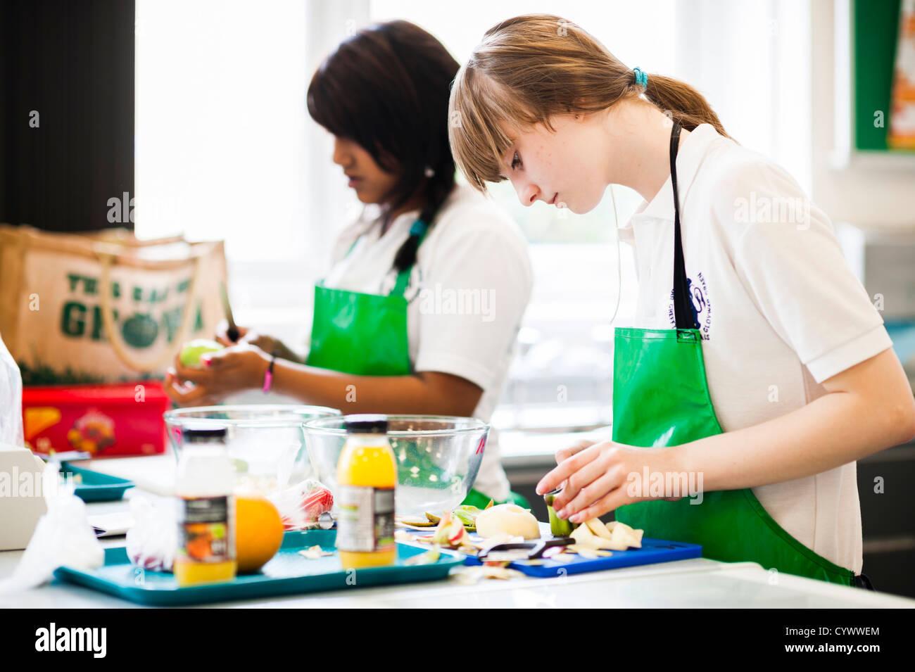 Due ragazze preparare le verdure in una tecnologia alimentare classe di cucina presso una scuola secondaria, Wales Immagini Stock