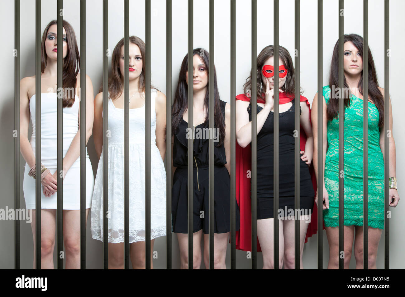 Donna in costume da supereroe con amici di sesso femminile in piedi behinds sbarre della prigione Immagini Stock