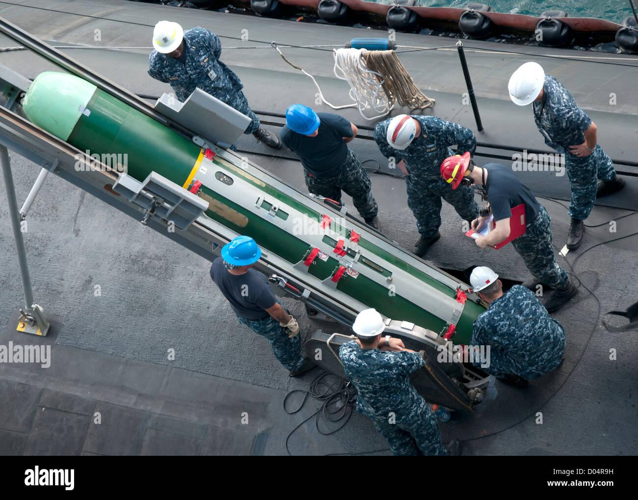 I marinai dal sommergibile offerta USS Frank Cable rimuovere un contrassegno 48 funzionalità avanzata torpedo Immagini Stock