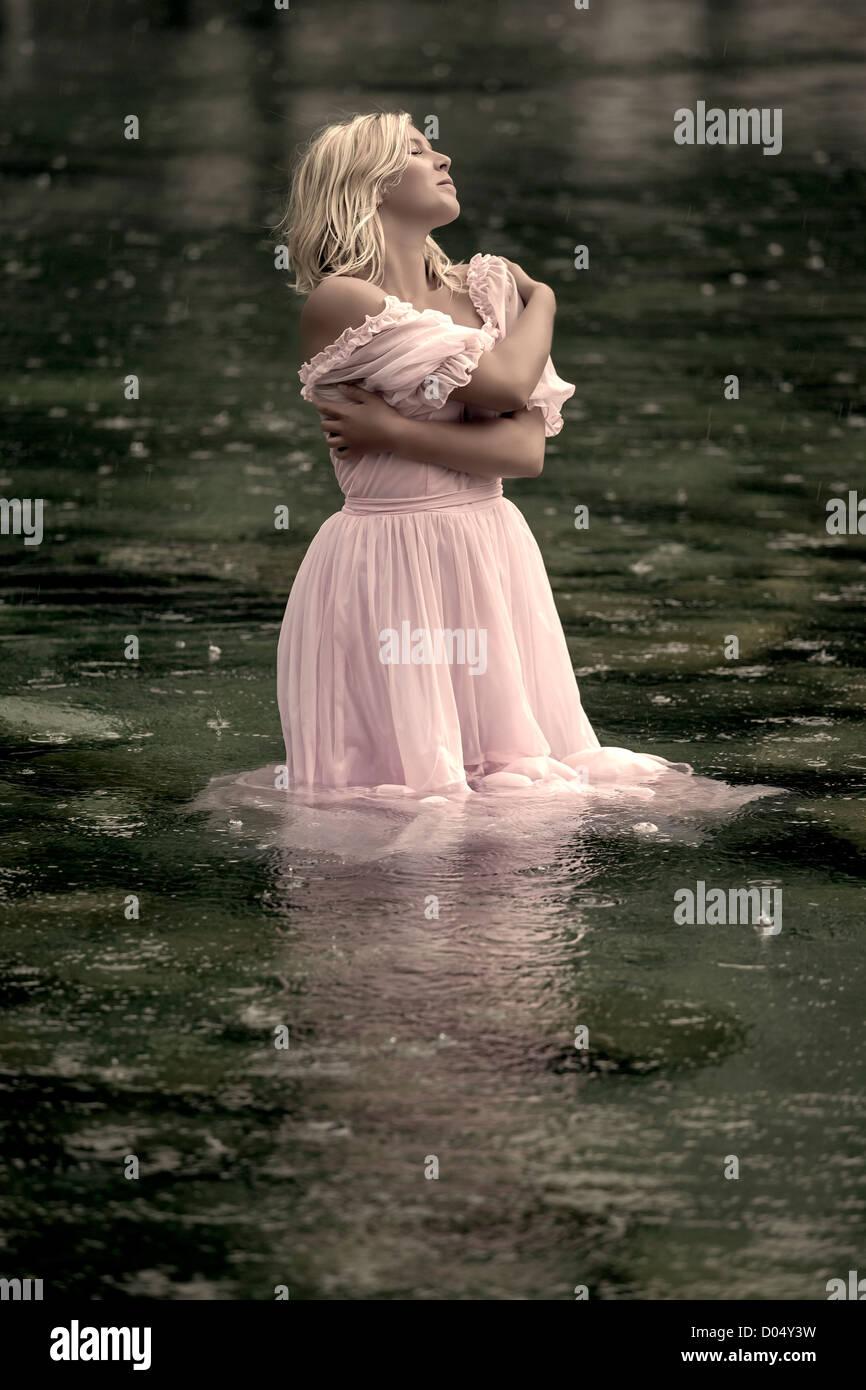 Una donna in piedi in acqua e godendo la pioggia Immagini Stock