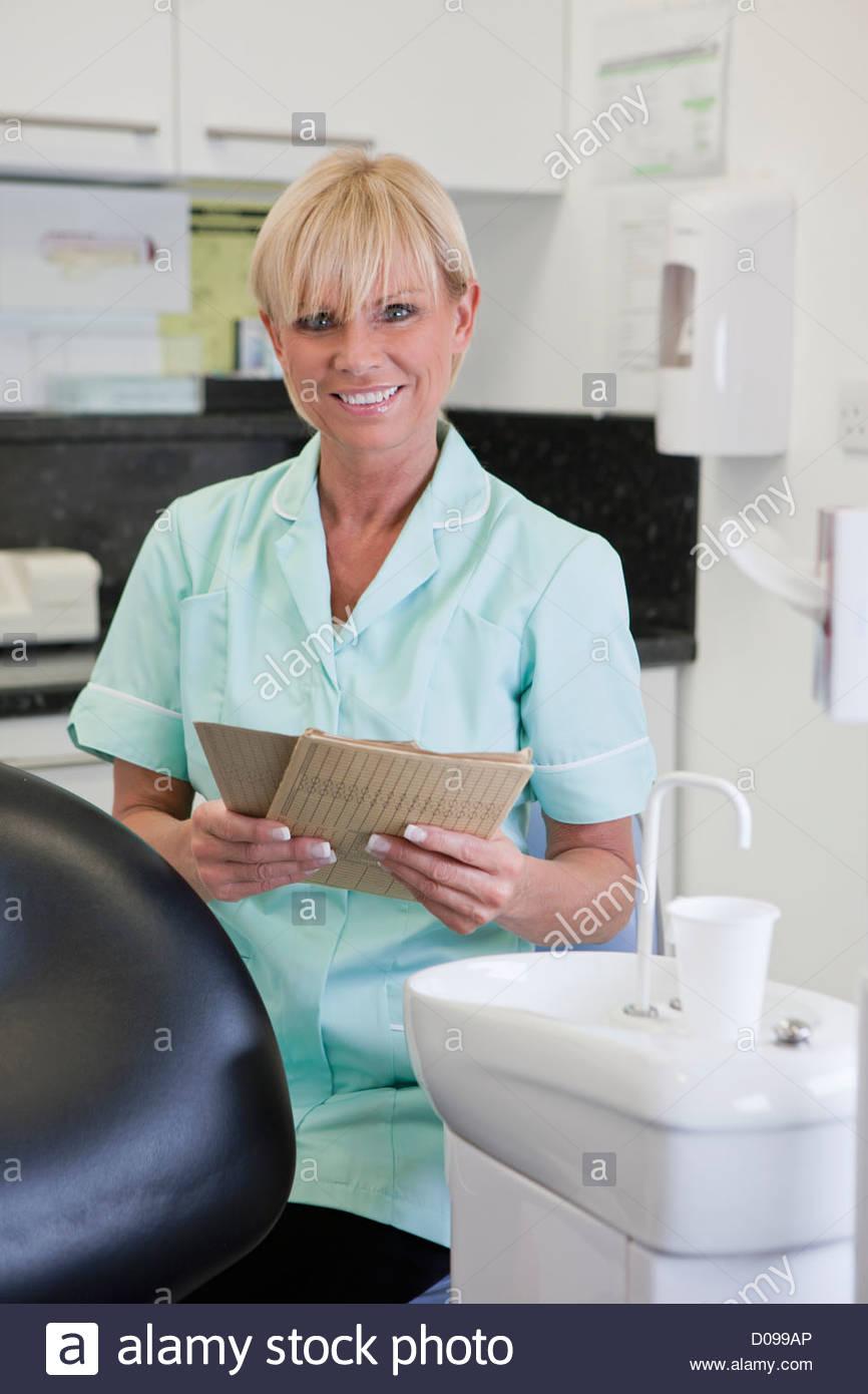 Una femmina di infermiere dentali azienda dentale del paziente i record Immagini Stock