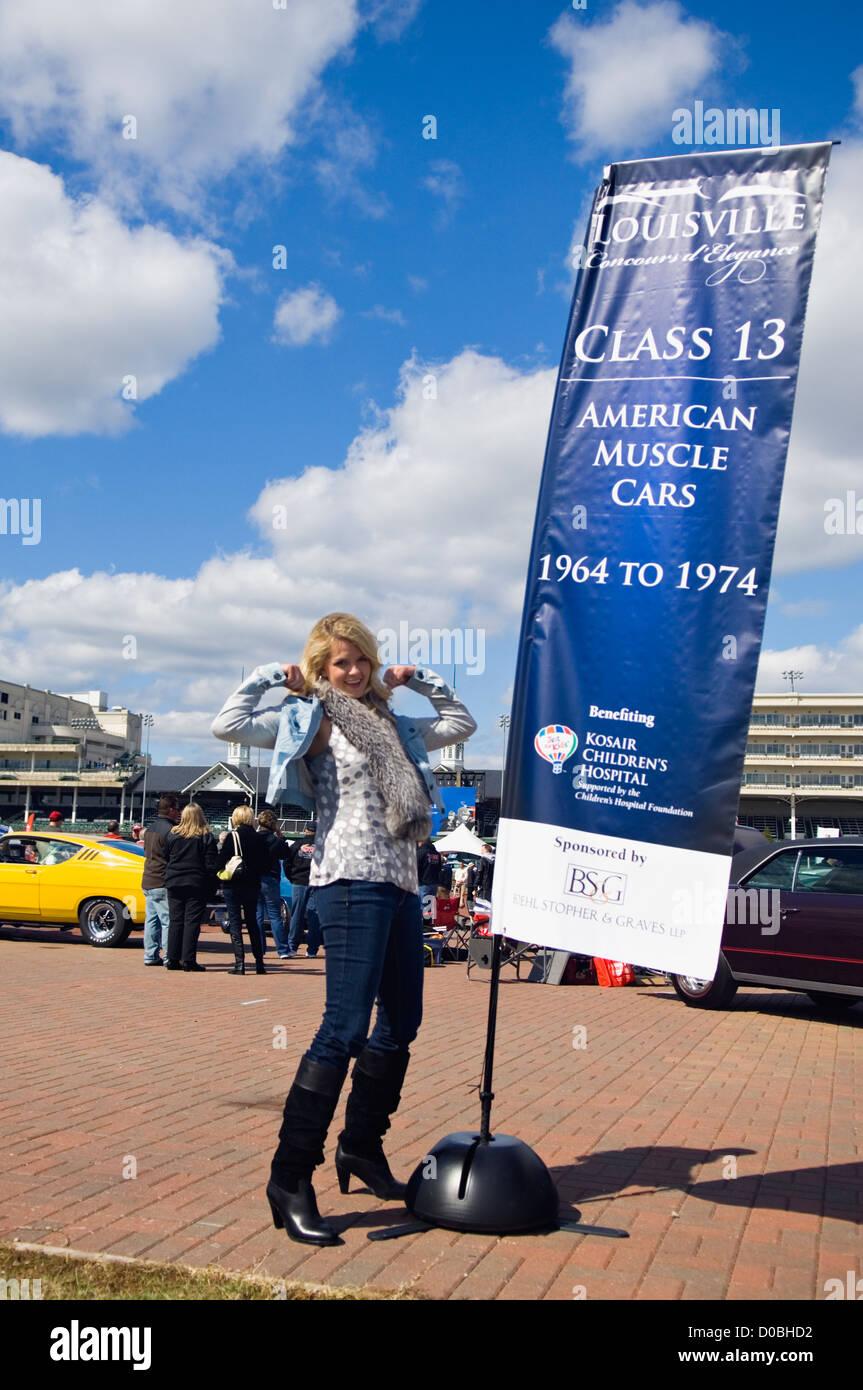 Modello in 70's abbigliamento ponendo accanto all Muscle Car Banner in 2012 Concours d'Eleganza a Churchill Immagini Stock