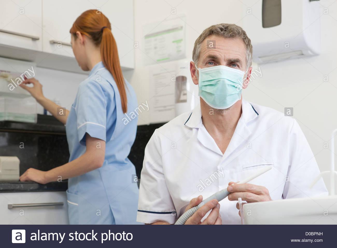 Un dentista maschio e femmina infermiere dentali in una chirurgia dentale Immagini Stock