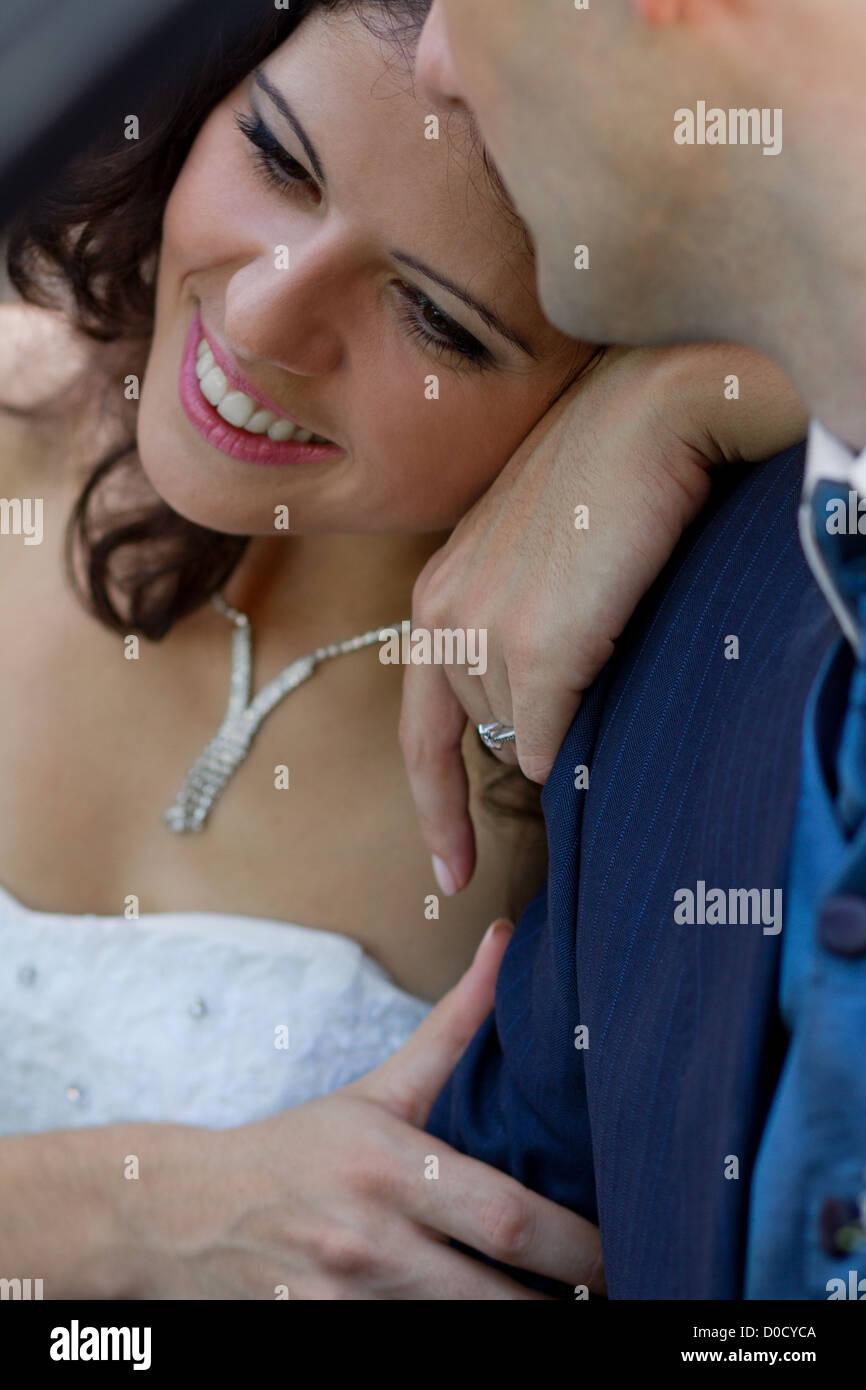 Felice giovane sposa appoggiata sulla sua spalla forte Foto Stock