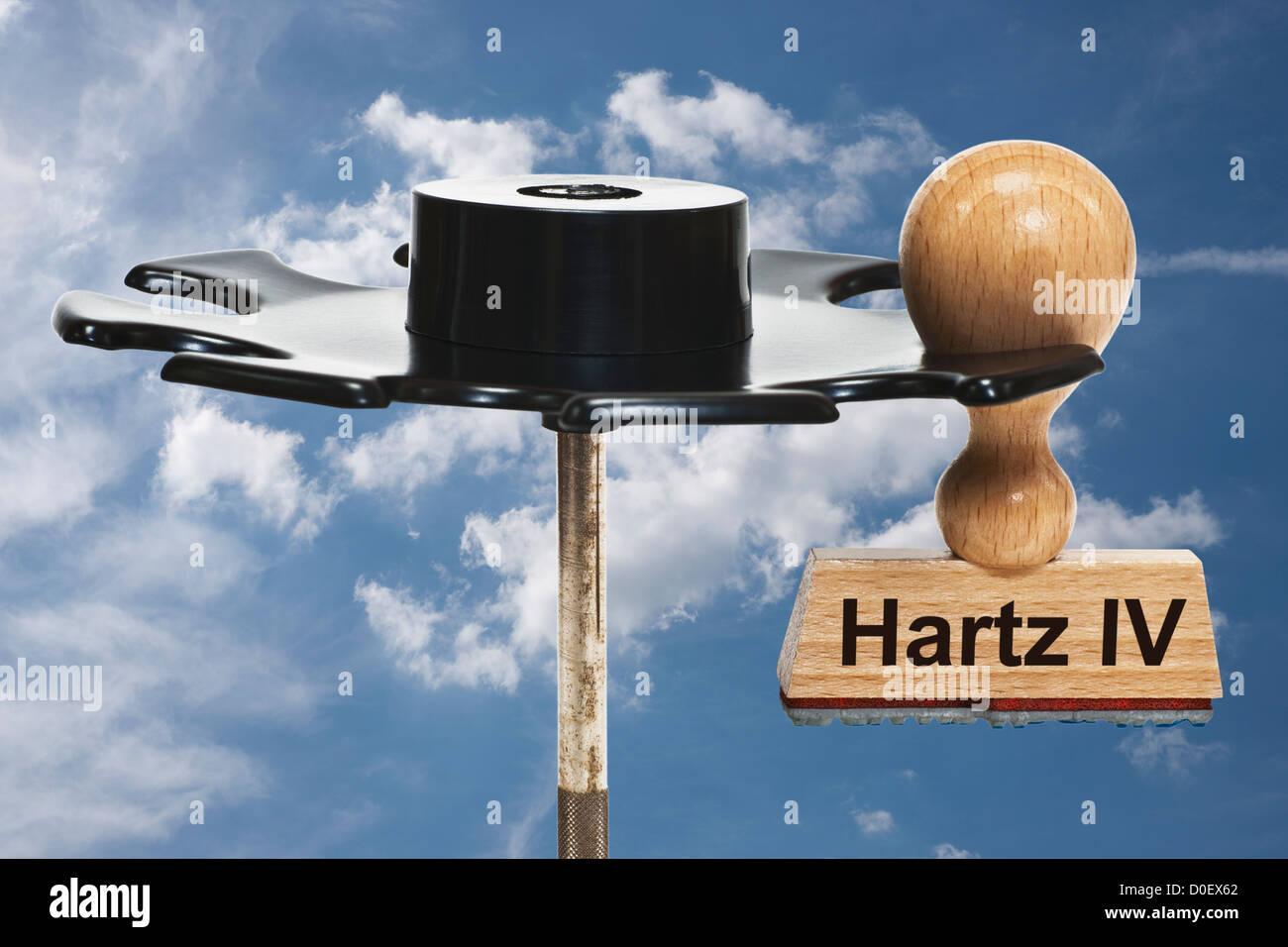 Timbro con iscrizione tedesca Hartz IV (sociale) si blocca in un rack di timbro, sfondo cielo Immagini Stock
