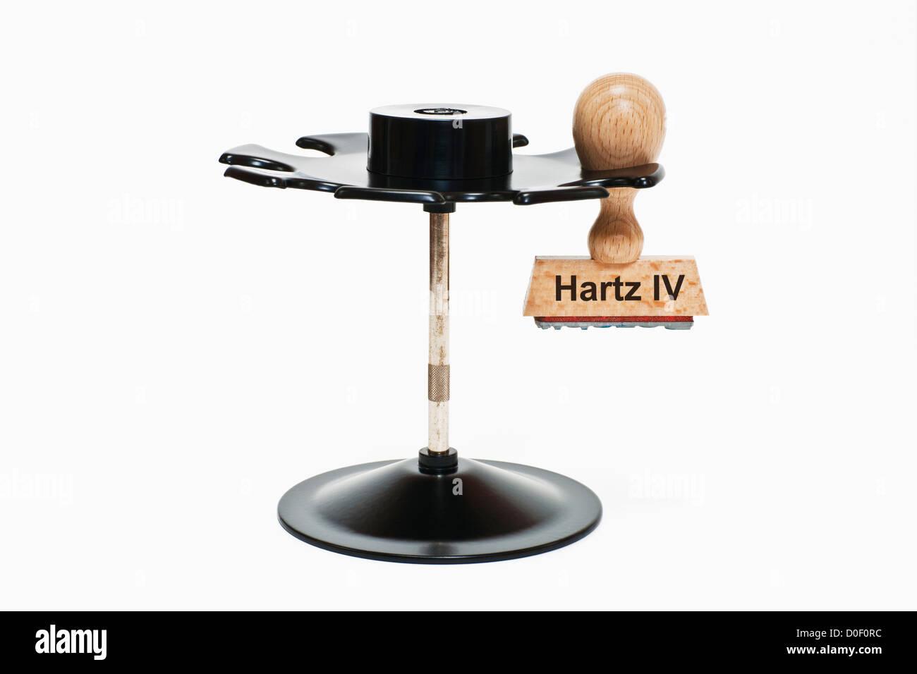 Timbro con iscrizione tedesca Hartz IV (sociale) si blocca in un timbro rack, sfondo bianco Immagini Stock