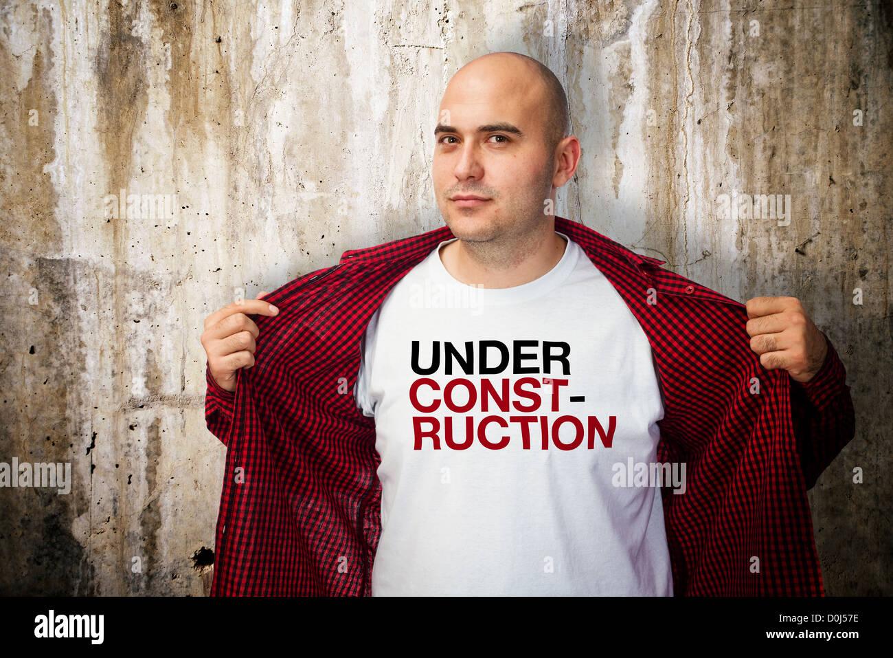 Uomo che indossa una camicia bianca con sotto il messaggio di costruzione Immagini Stock
