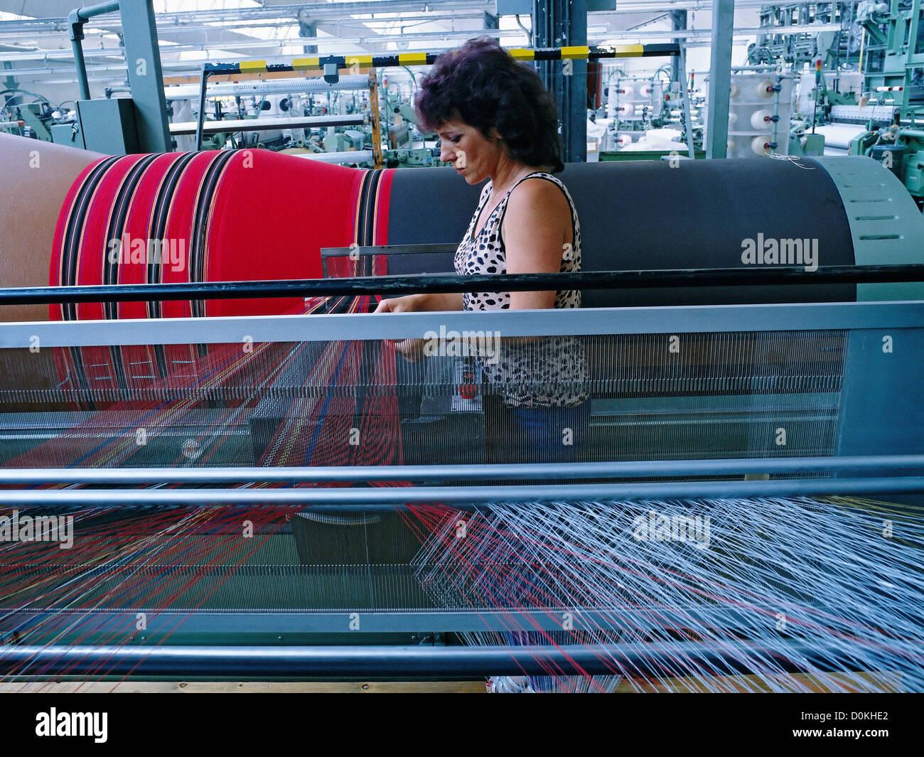 Un operaio tessile in corrispondenza di una sezione di orditoio in una  tessitura di mulino Foto stock - Alamy
