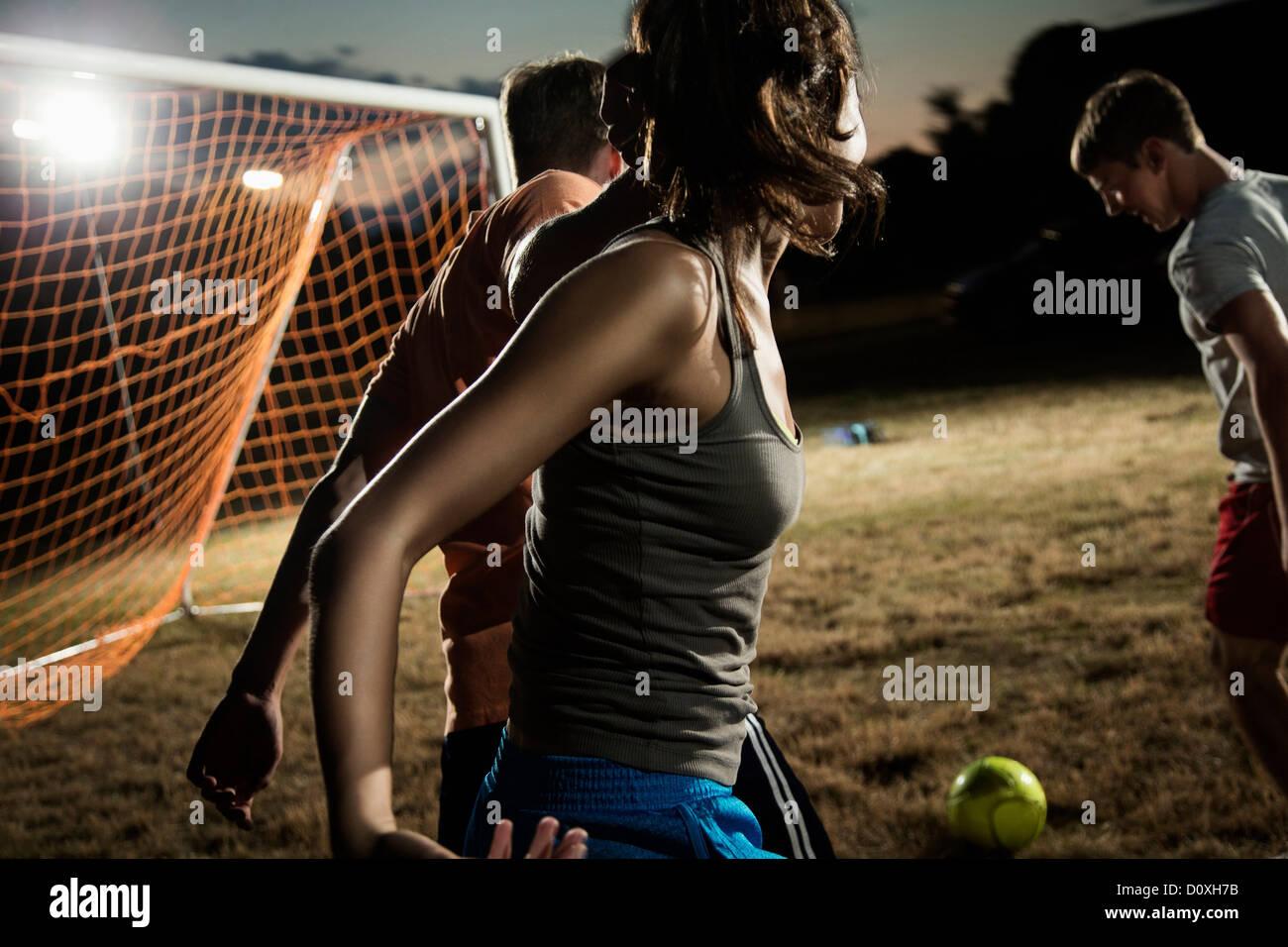 Gli amici che giocano a calcio di notte Immagini Stock