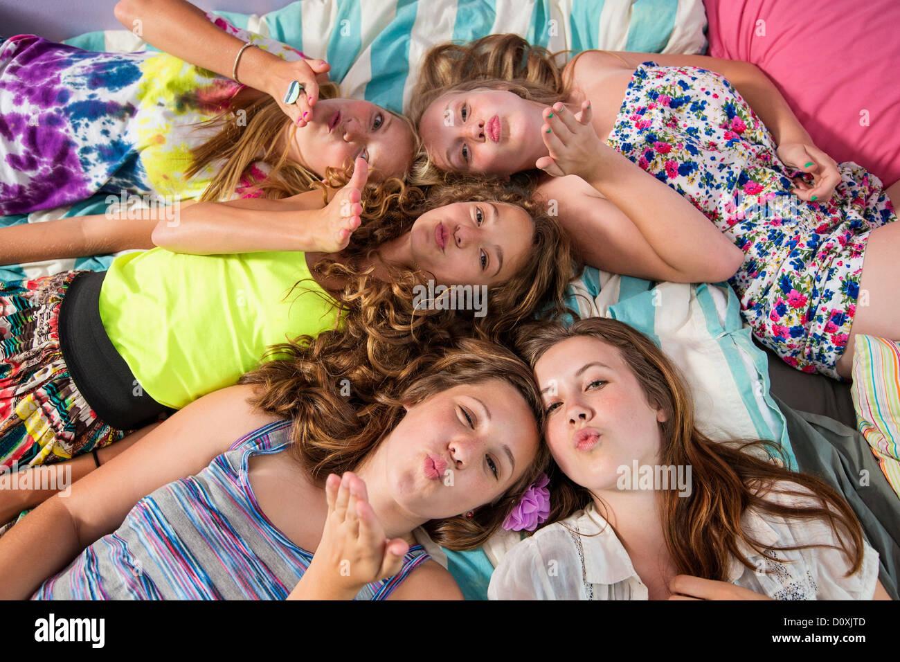 Ragazze giacente sul letto, baci di soffiatura Immagini Stock