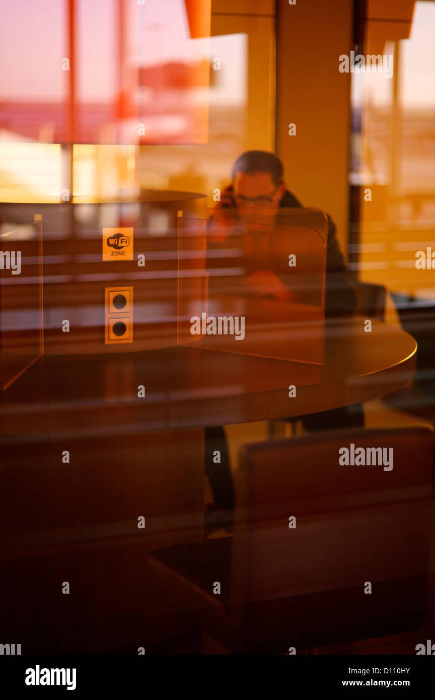 Uomo seduto dietro la parete di vetro in un aeroporto internazionale Immagini Stock