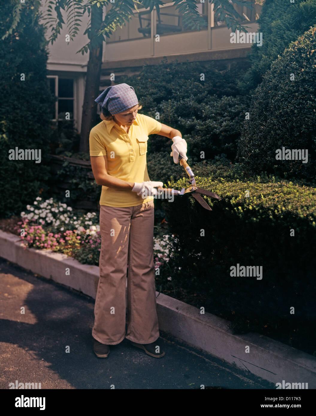Anni Settanta DONNA CON GIARDINO CLIPPERS TRIMMING siepe di bosso indossando BELLBOTTOMS Immagini Stock