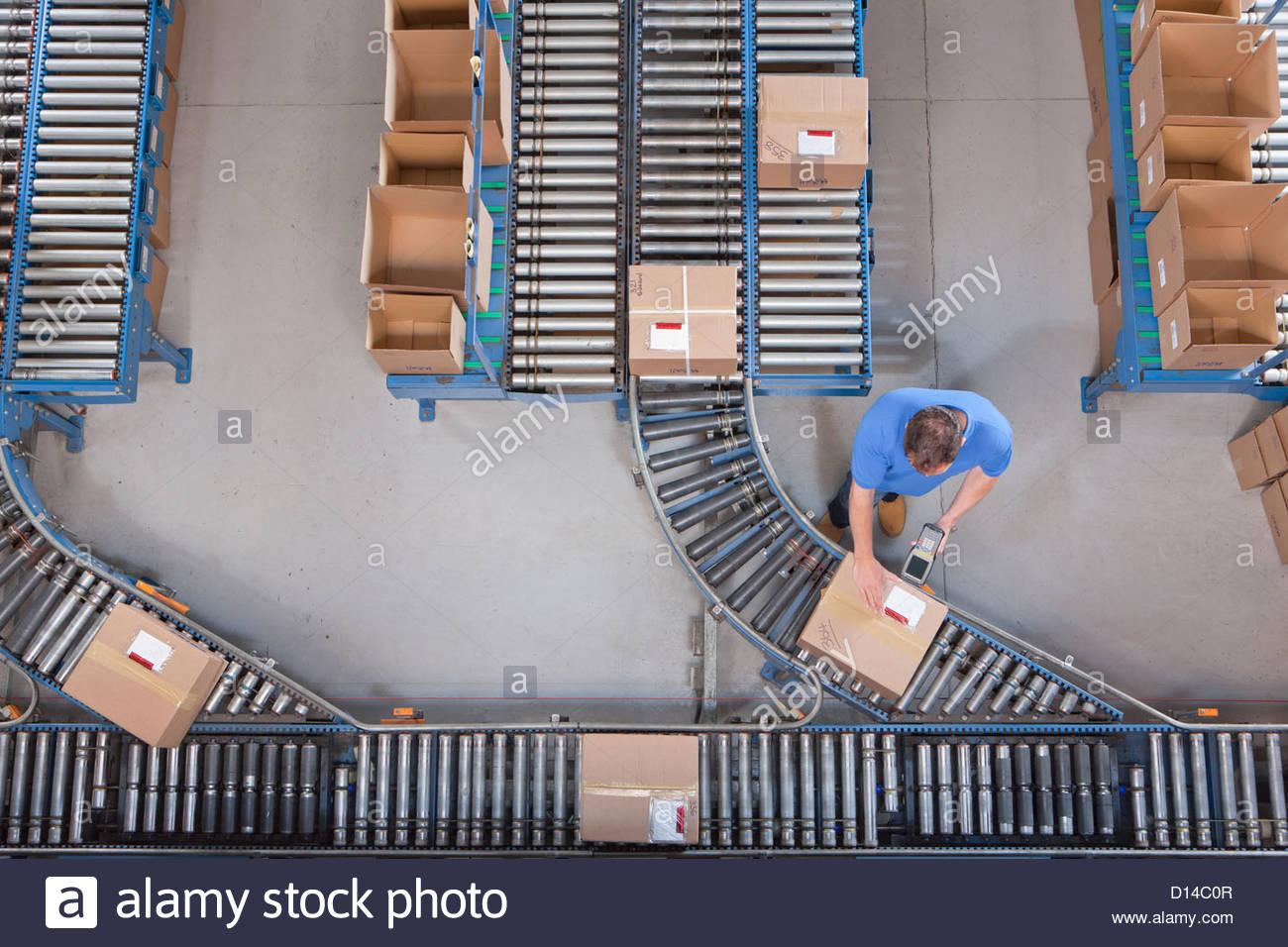 Lavoratore con lettore di codice a barre la scansione casella sul nastro trasportatore in magazzino di distribuzione Immagini Stock