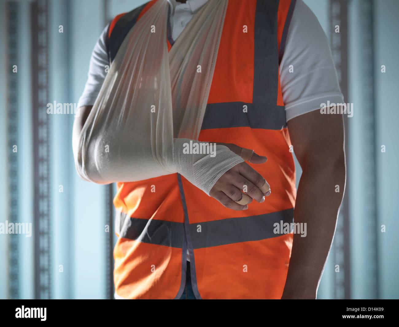 Chiusura del lavoratore con braccio in imbracatura Immagini Stock