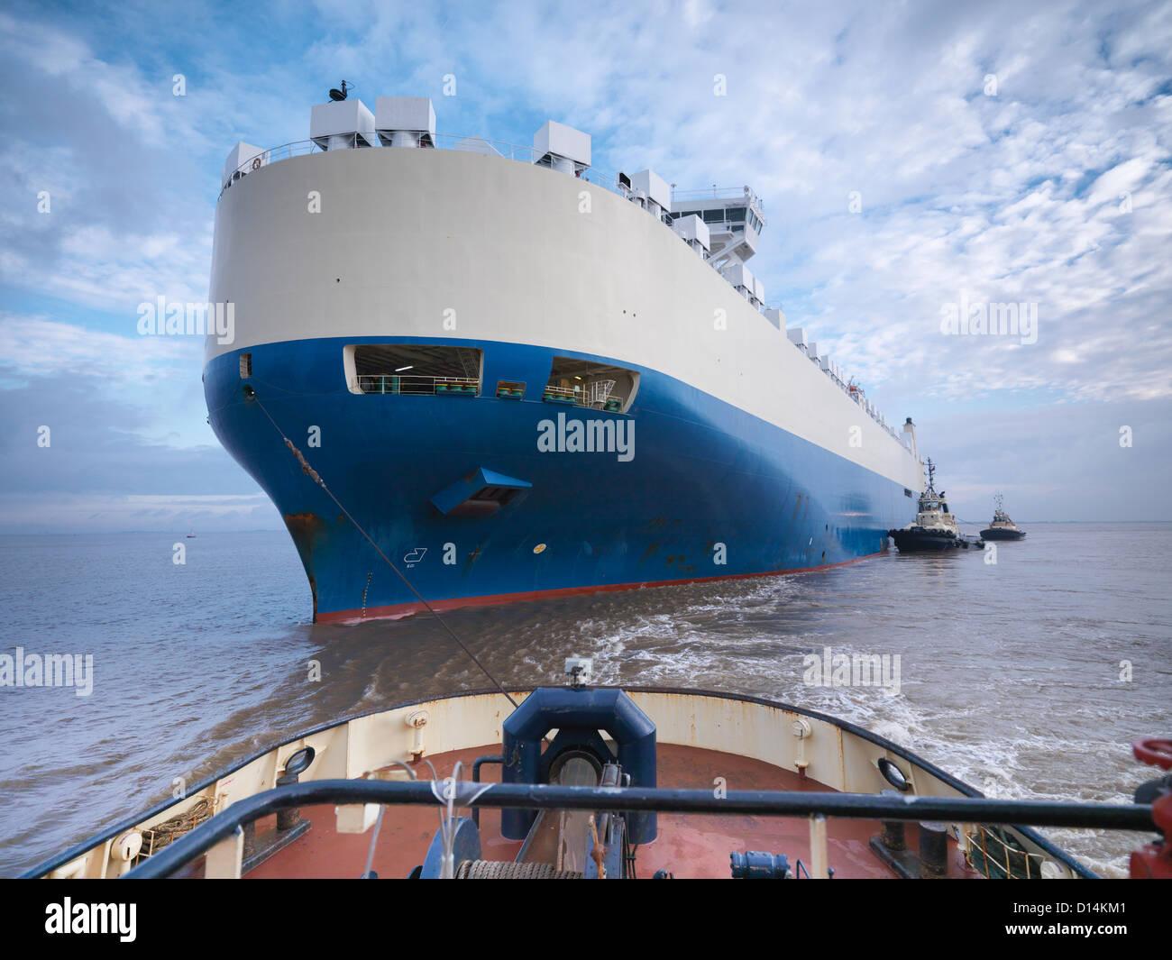 Rimorchiatore spinge grande barca in mare Immagini Stock