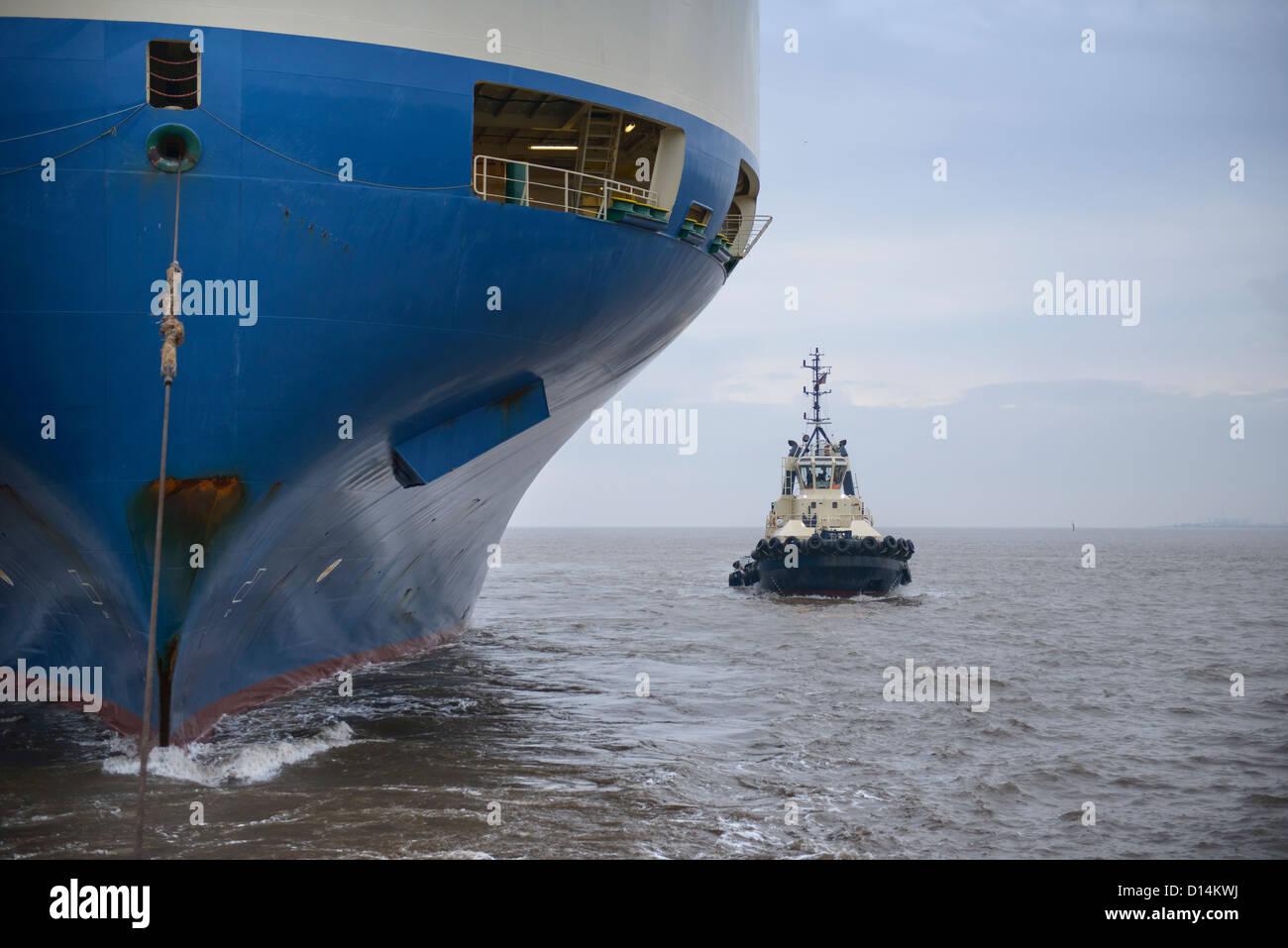 Rimorchiatore vela dalla nave di grandi dimensioni Immagini Stock
