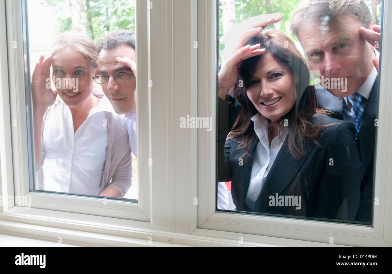 La gente del peering in windows di casa Immagini Stock