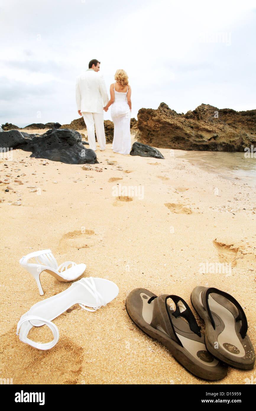 Coppie in viaggio di nozze a piedi lungo la spiaggia lasciando dietro di sé Orme  nella sabbia e le calzature in primo piano c972cd81a3e