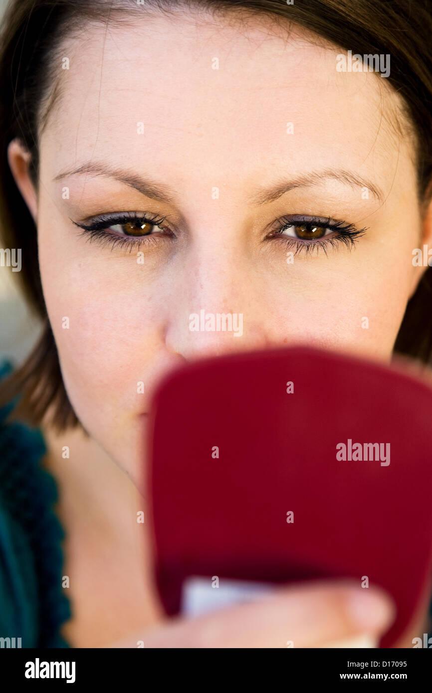 Berlino, Germania, giovane donna cercando in mano lo specchio Foto Stock