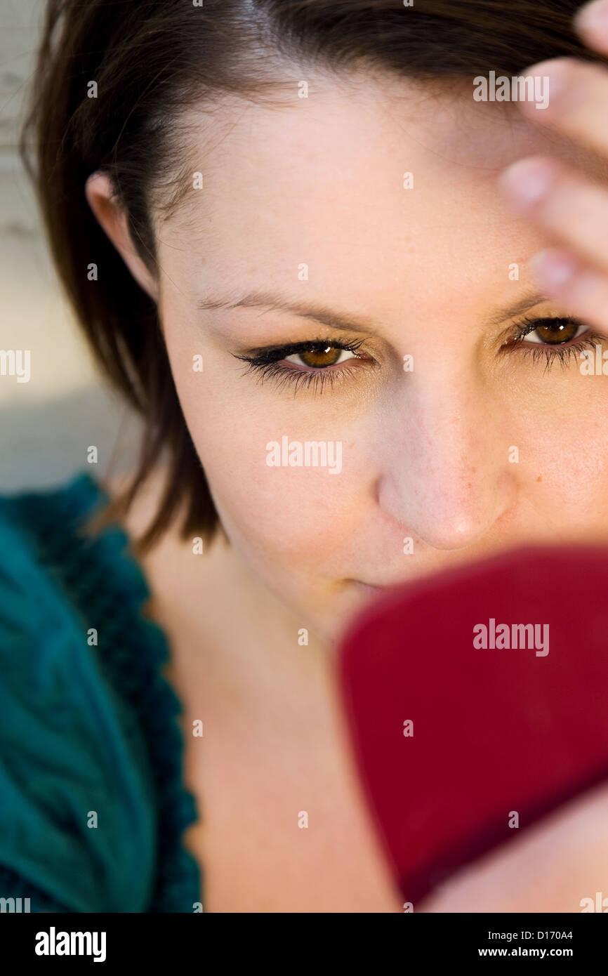Berlino, Germania, giovane donna cercando in mano lo specchio Immagini Stock