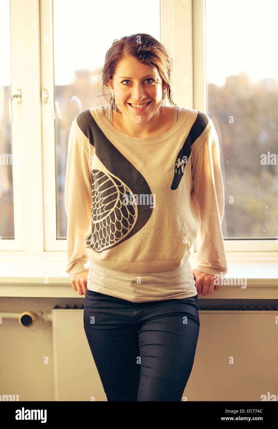 Ritratto di un sorridente giovane donna in interni con una finestra su sfondo di lei Immagini Stock