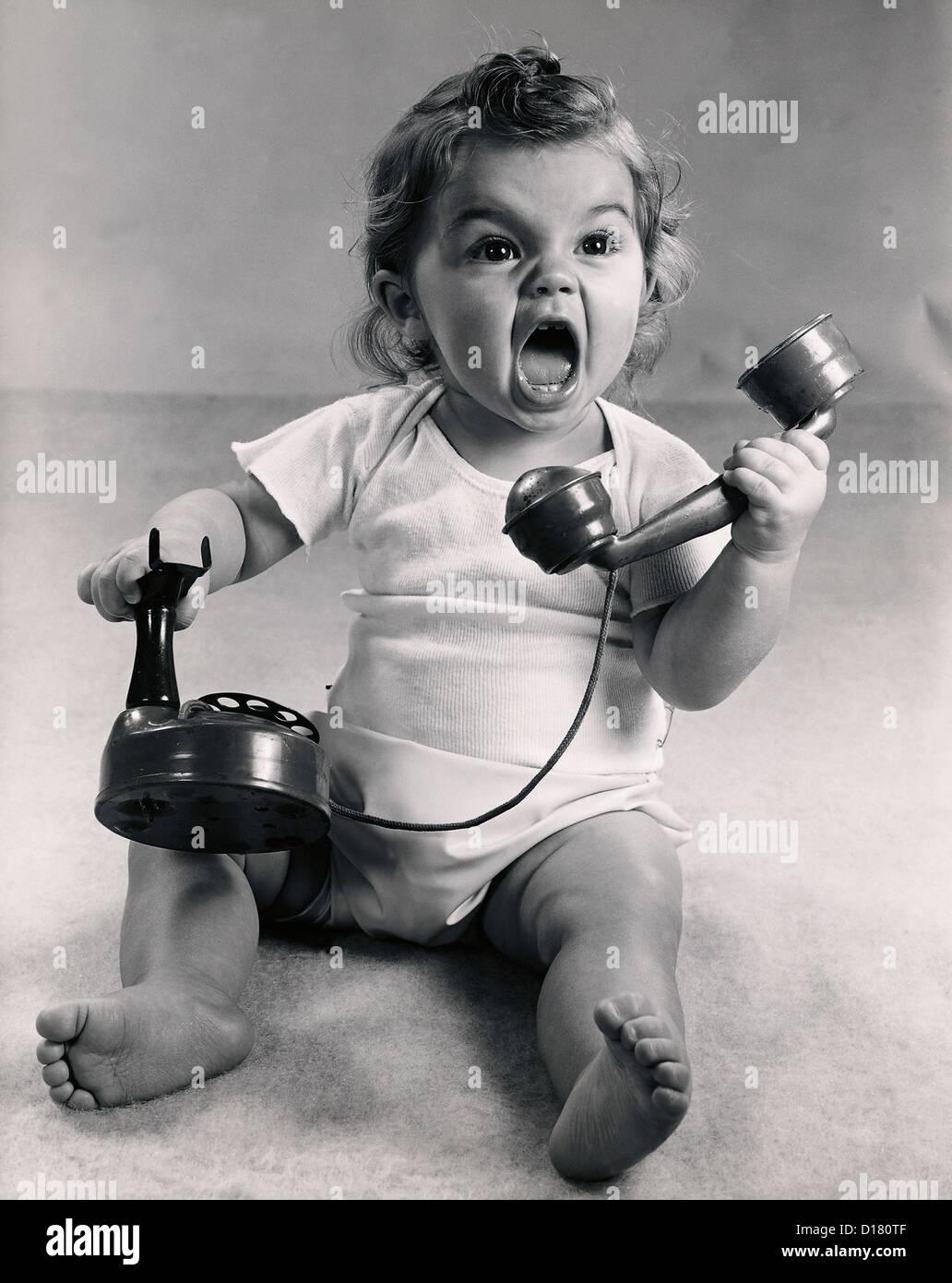 Foto d'epoca del neonato urlando con telefono Immagini Stock