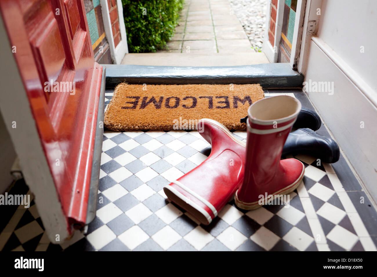 Tappeto di benvenuto e gli stivali da pioggia Immagini Stock