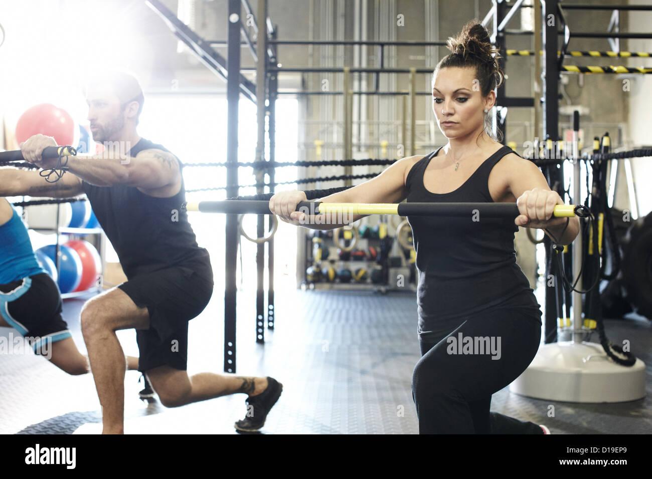 La donna che lavora fuori in palestra con esercizio bar e cavo di resistenza Immagini Stock