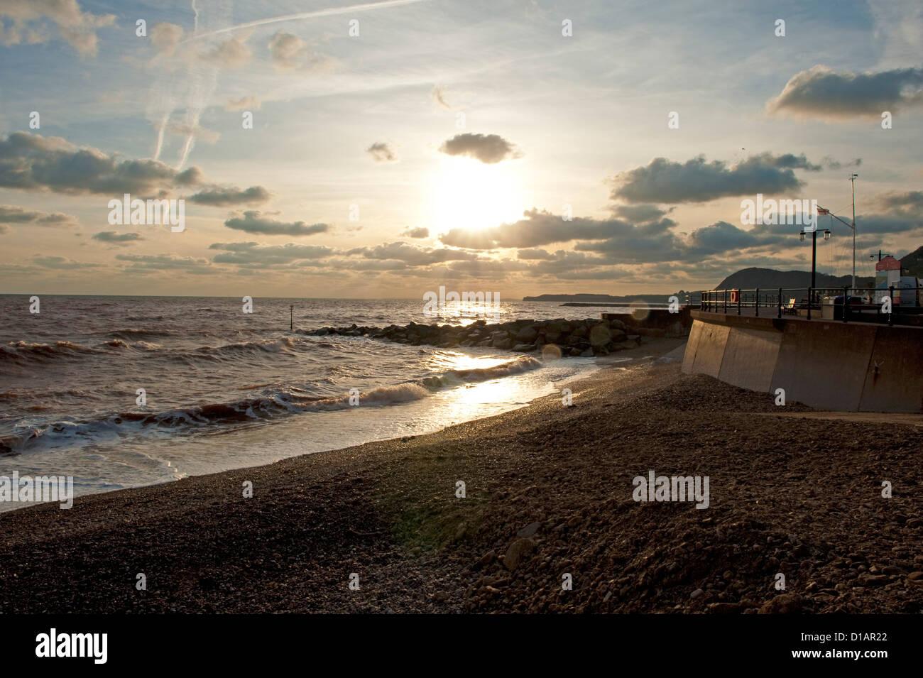 Pomeriggio di sole invernale impostazione sul mare, i frangiflutti e spiaggia di ciottoli a Sidmouth in East Devon Immagini Stock
