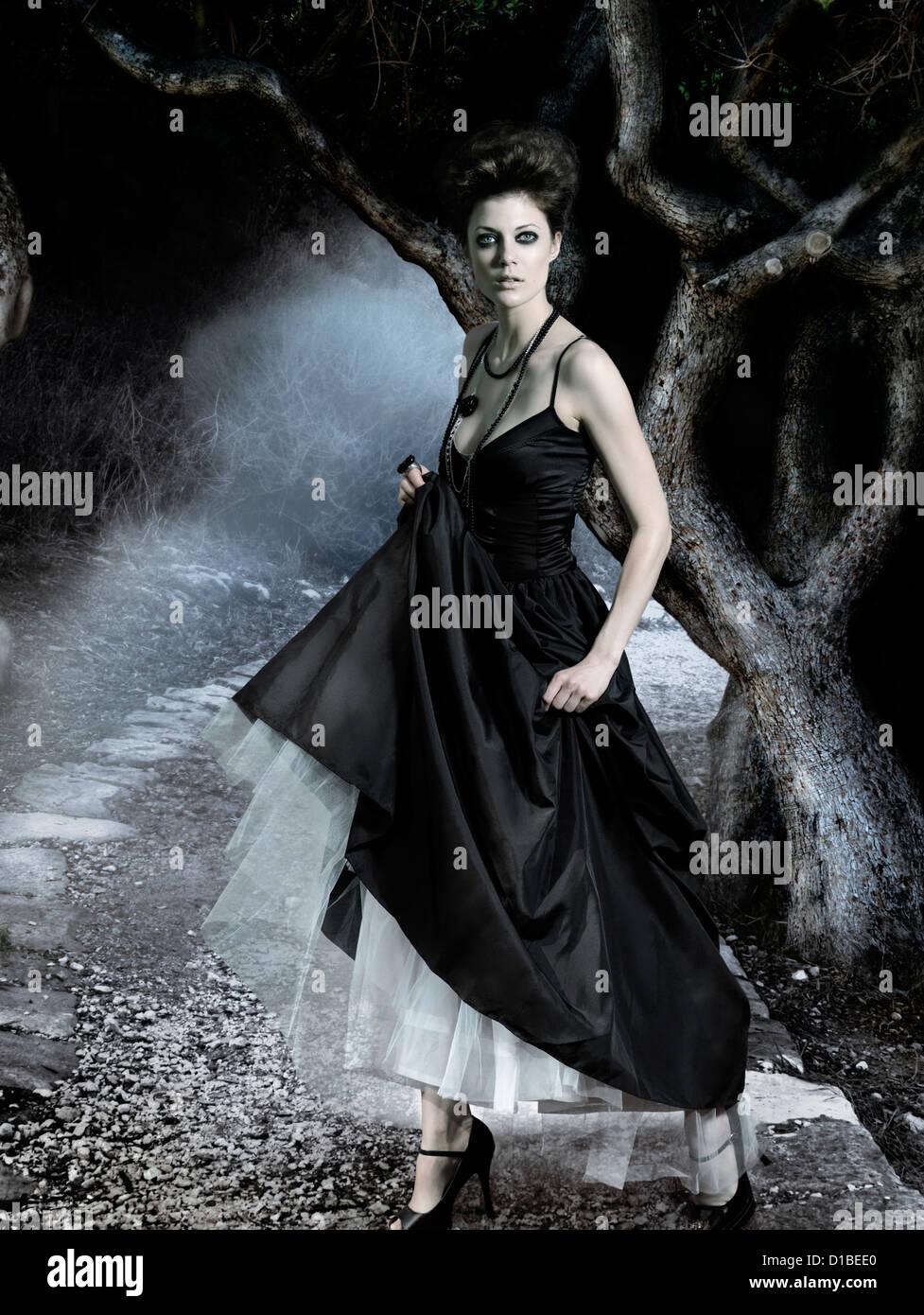 Giovane e bella donna che indossa lungo classico abito nero in una oscura foresta misteriosa. In modo digitale immagine Immagini Stock