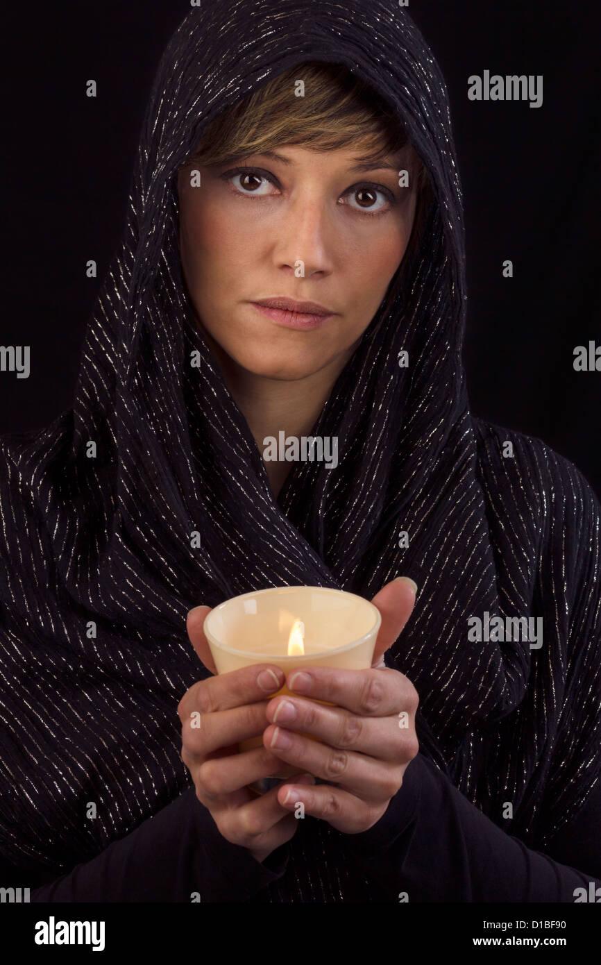 Bella giovane donna in nero capo azienda una candela che brucia nelle sue mani e guardando pensieroso alla fotocamera. Foto Stock