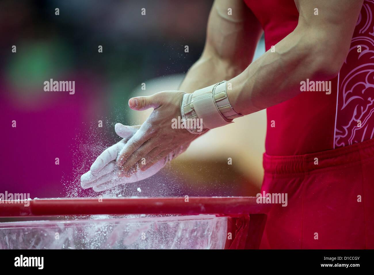 Dettaglio dei maschi di ginnasti mani applicazione chalk durante l'uomo ginnastica completa individuale al 2012 Immagini Stock
