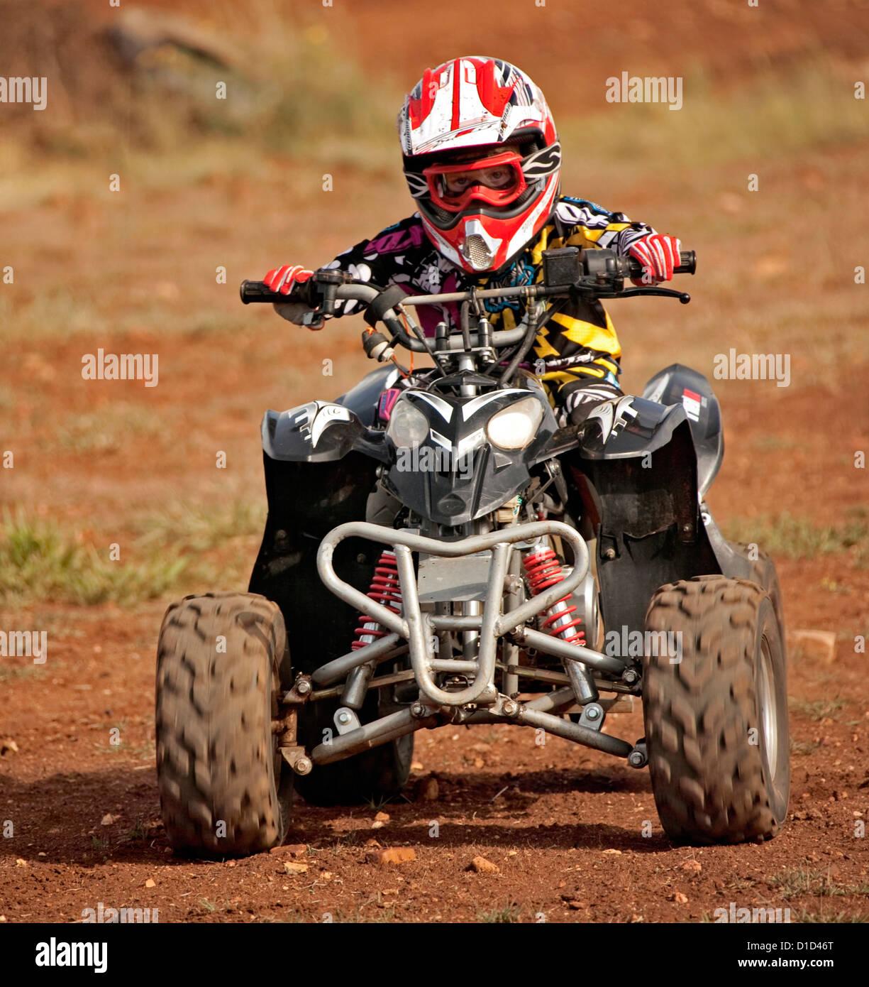 Bambino - di età compresa tra i quattro - su quad bike indossando un abbigliamento protettivo e cavalcare su Immagini Stock