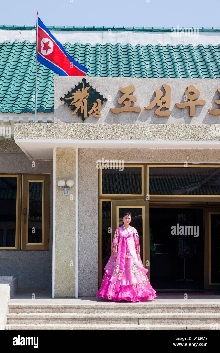Donna in variopinti costumi tradizionali in entrata al negozio di souvenir, Repubblica Popolare Democratica di Corea Immagini Stock