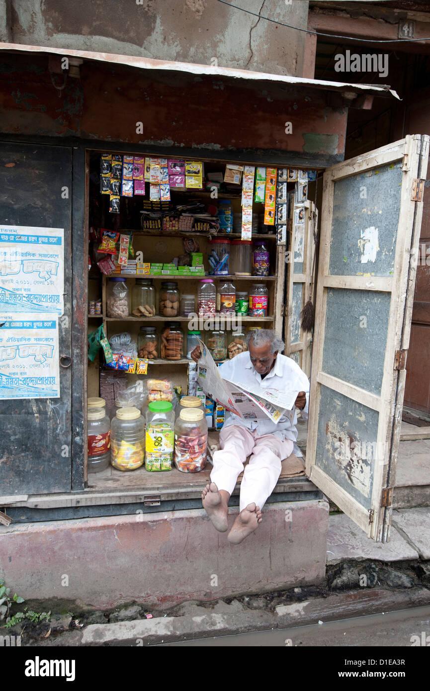 Proprietario di un negozio di leggere il giornale la mattina, Calcutta, West Bengal, India, Asia Immagini Stock