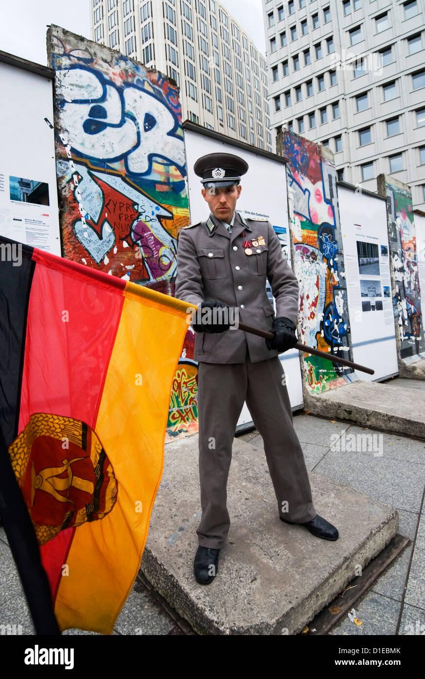 Oriente guardia tedesco con l'ex RDT bandiera di fronte i resti del muro di Berlino e Potsdamer Platz di Berlino, Foto Stock