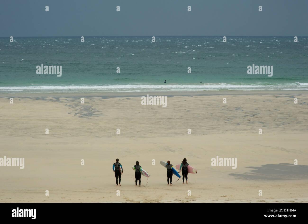 Quattro surfisti in mute che trasportano le schede Rubrica e giù per la spiaggia di St. Ives, Cornwall, Inghilterra Immagini Stock