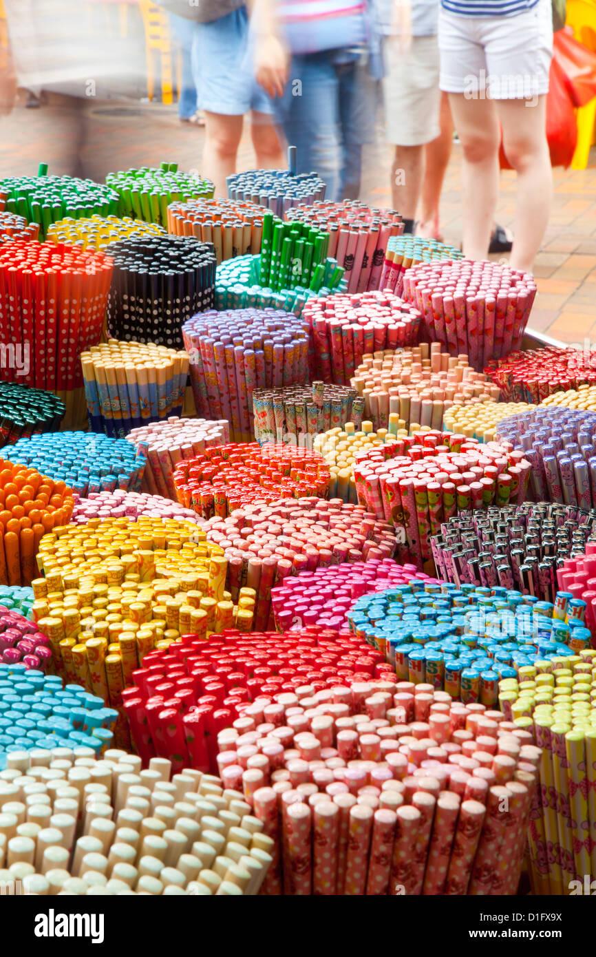 Decorative colorate bacchette per la vendita come souvenir ai turisti nel mercato di Chinatown, Temple Street, Singapore, Immagini Stock