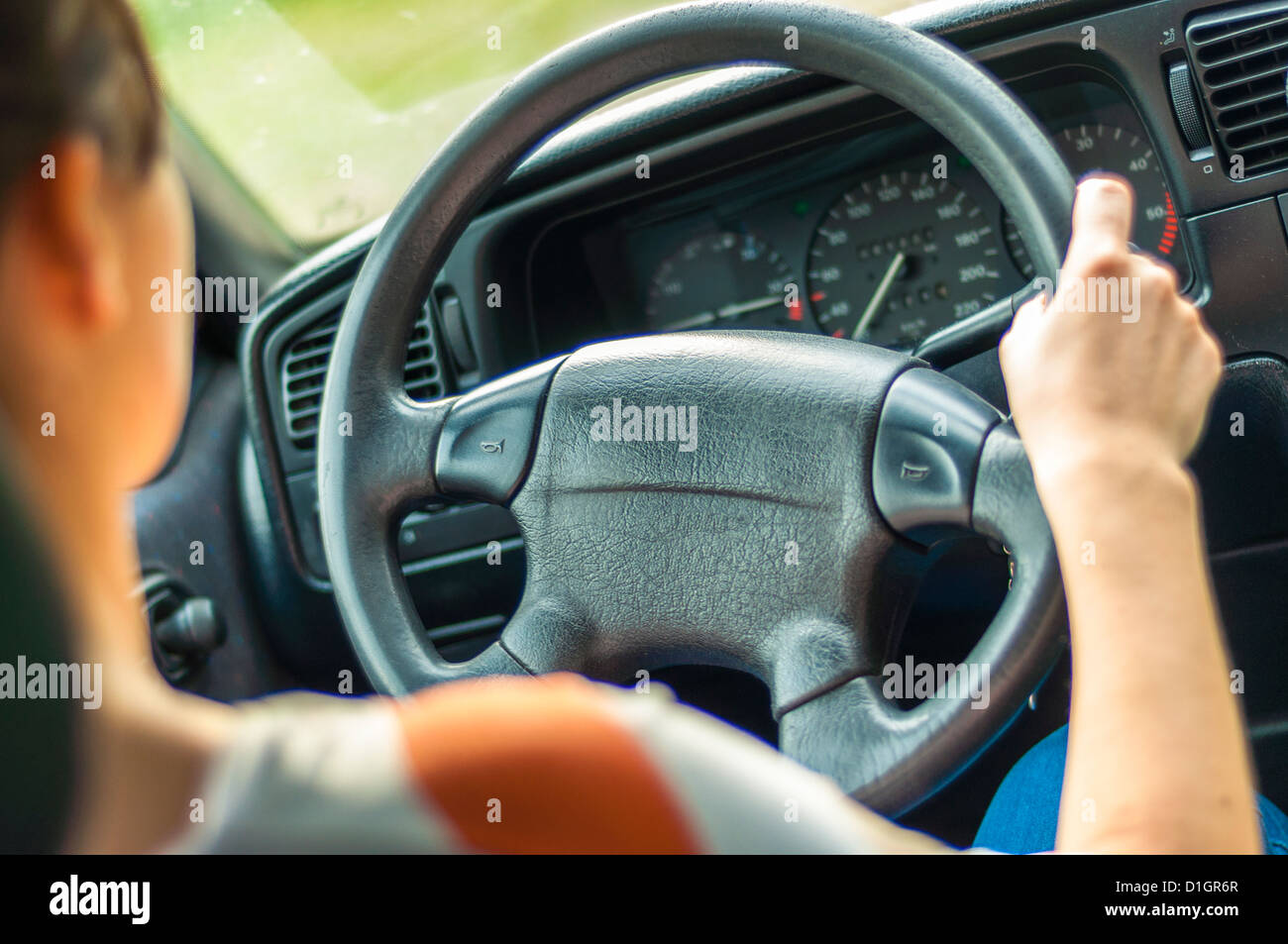 Le mani di una femmina di conducente sul volante Immagini Stock