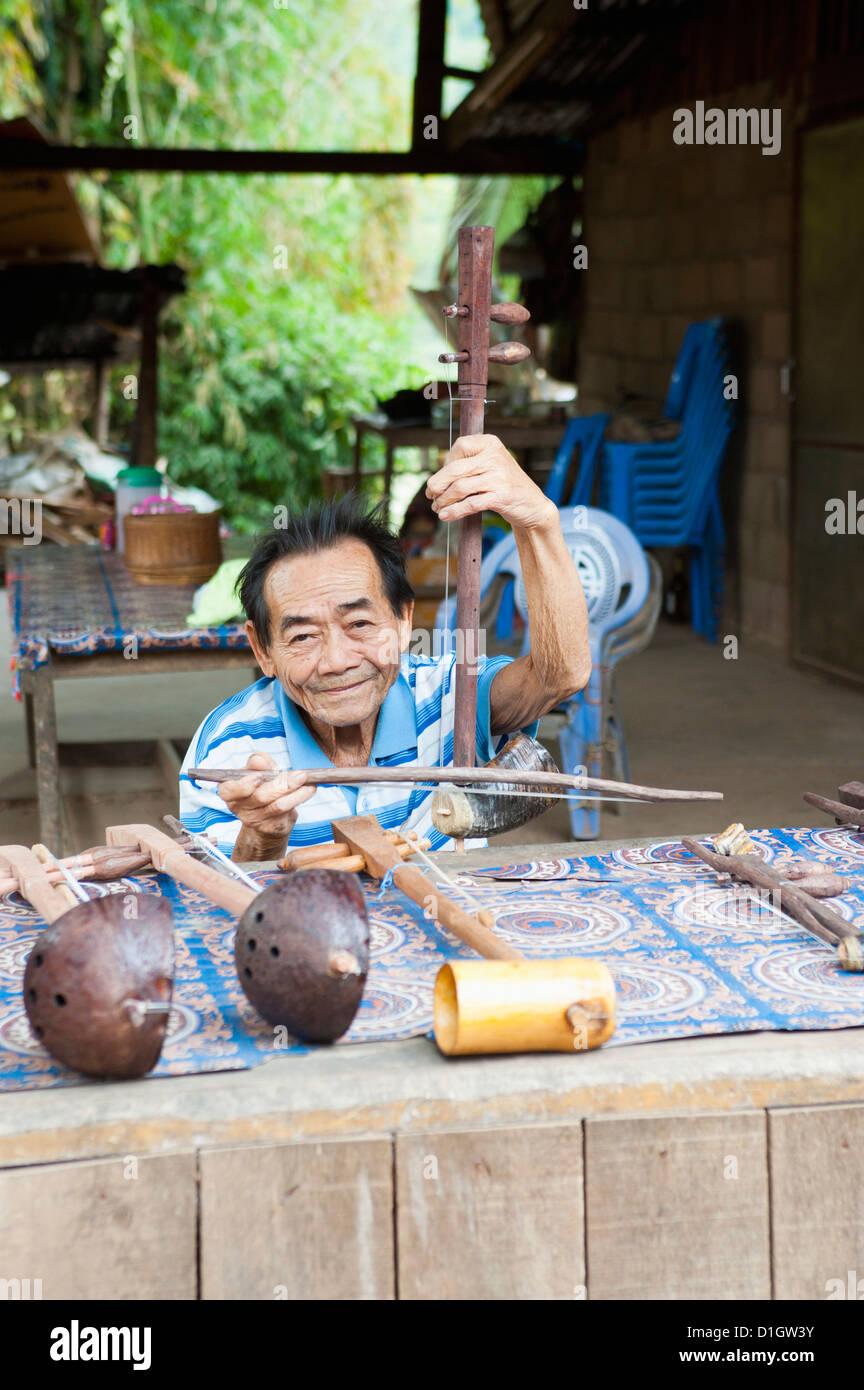 L'uomo la riproduzione artigianale di strumento musicale venditore, Luang Prabang, Laos, Indocina, Asia sud Immagini Stock