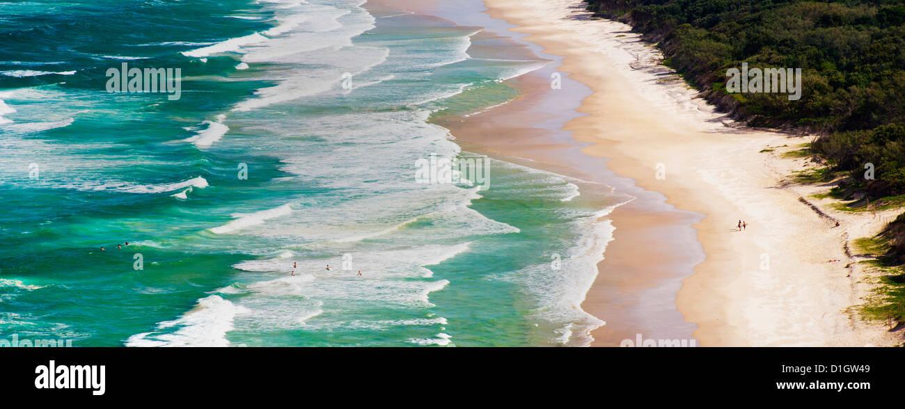 Foto panoramica di surfers di uscire a navigare sul sego spiaggia di Cape Byron Bay, Nuovo Galles del Sud, Australia Foto Stock