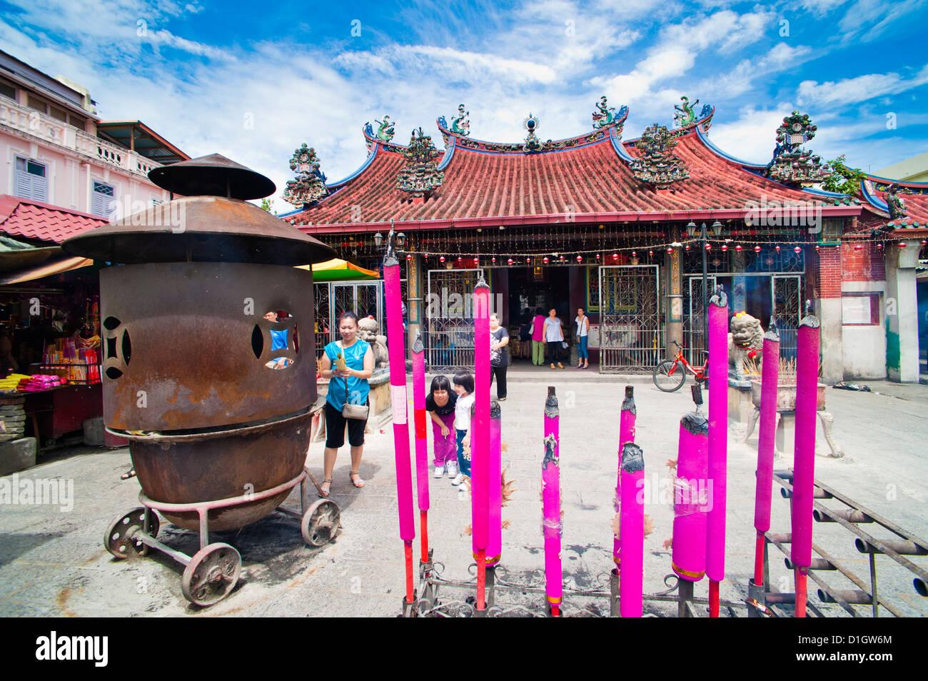 Malaysian persone in preghiera dietro grandi bastoni di incenso in un tempio buddista di George Town, Penang, Malaysia, Immagini Stock