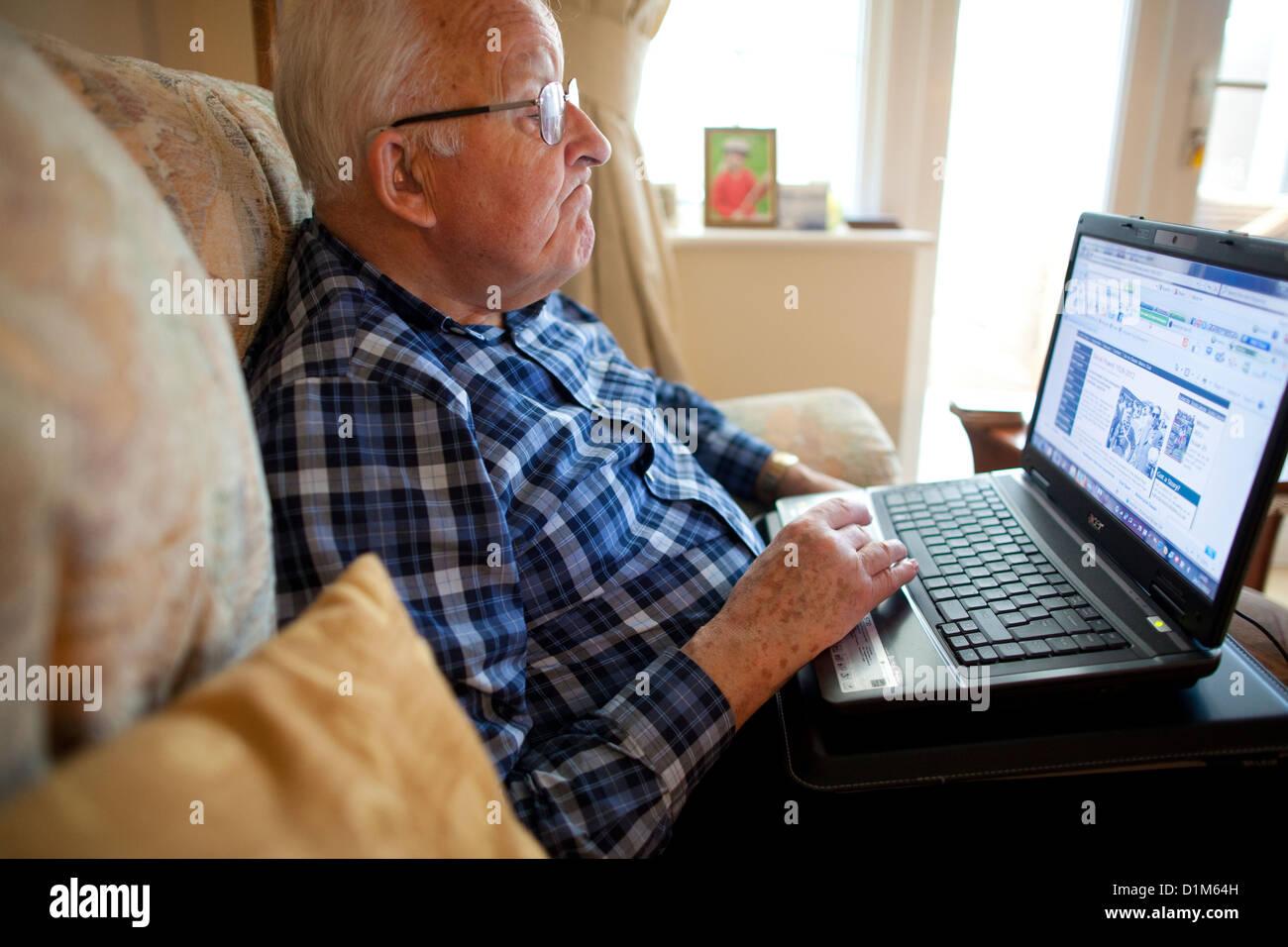 Uomo anziano usando un computer portatile a casa Immagini Stock