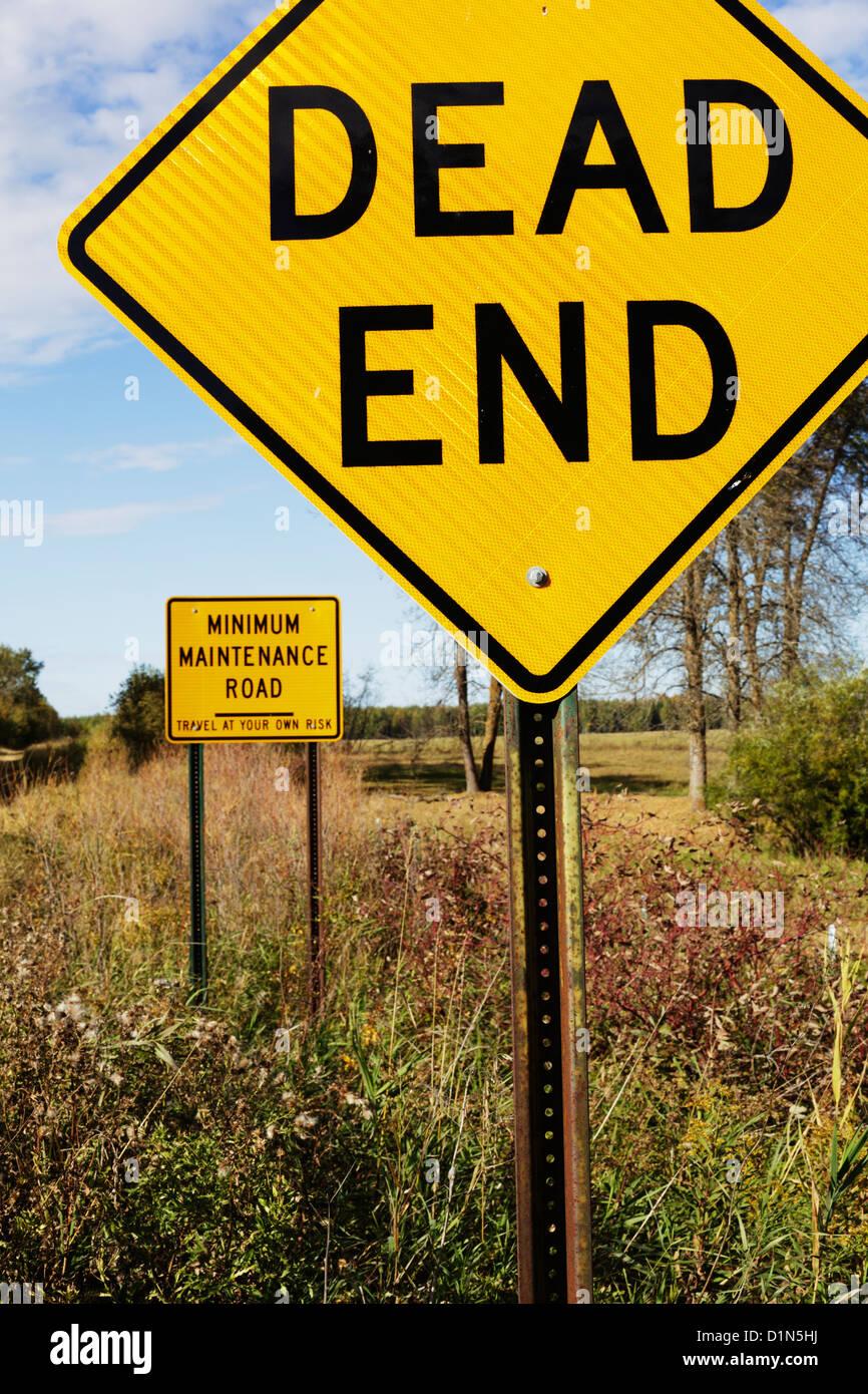 Dead End firmare con un minimo di manutenzione cartello stradale dietro. Immagini Stock