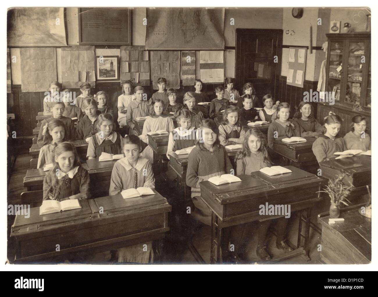 Scuola di fotografia junior ragazze seduti alla scrivania con libri aperti in aula avendo una lezione - 1930, U.K. Immagini Stock